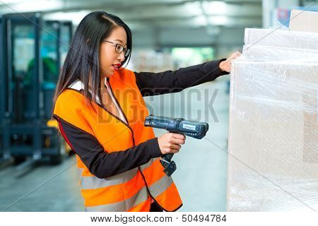 Logistics - female worker or shipper with protective vest and scanner, scans bar-code of package, he standing at warehouse of freight forwarding company