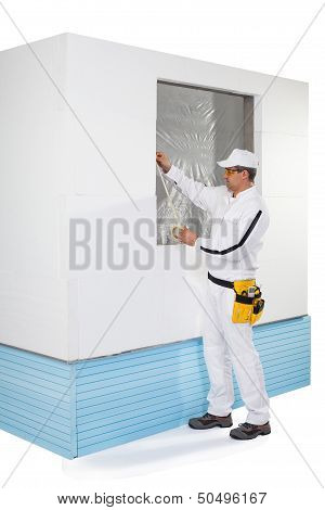Worker Taping A Frame Of Window With A Masking Tape
