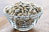 stock photo of sunflower-seeds  - Shelled sunflower seeds close up in glass bowl - JPG