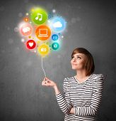 pic of balloon  - Pretty young woman holding colorful social media icons balloon - JPG