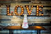 stock photo of banquet  - Image of a wedding cake with the word love as sinage on a rustic background - JPG