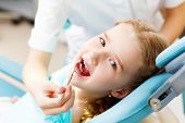 image of cavities  - Little girl sitting in the dentists office - JPG