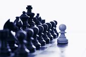 image of chess pieces  - White pawn challenging army of black chess pieces blue tone - JPG