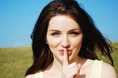 image of shh  - Beautiful young woman saying shh with a finger to her lips outdoors - JPG