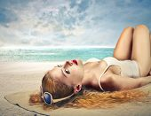 beautiful blonde woman sunbathing at the beach