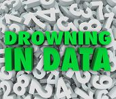 stock photo of overwhelming  - The words Drowning in Data on a sea of numbers illustrating an overabundance of numbers that are too overwhelming to understand - JPG