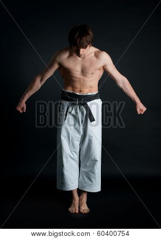 Man In A Kimono With A Black Belt Bows On Black Background