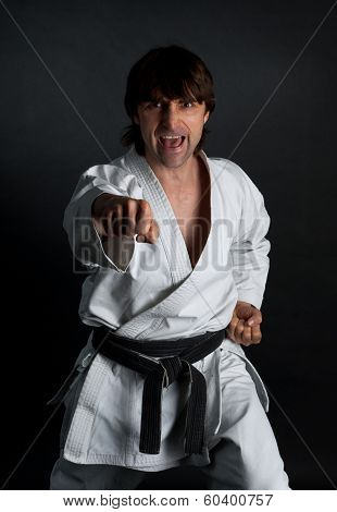 Man In A Kimono With A Black Belt Doing  Forward Kick On A Black Background