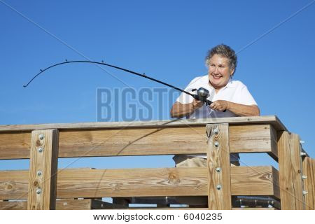 Senior Lady Reels In Fish