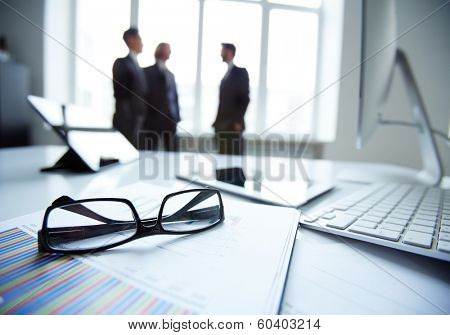 Technological devices, eyeglasses and financial document at workplace on background of three businessmen discussing ideas