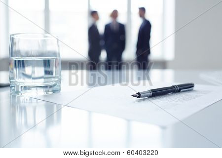 Image of business document, pen and glass of water at workplace with group of colleagues on background