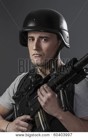 Gunfire, paintball sport player wearing protective helmet aiming pistol ,black armor and machine gun