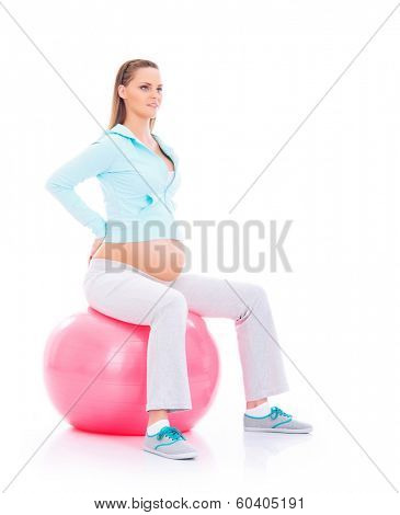 A young and fit pregnant blond woman working out with a pink fitness ball isolated on a white background.