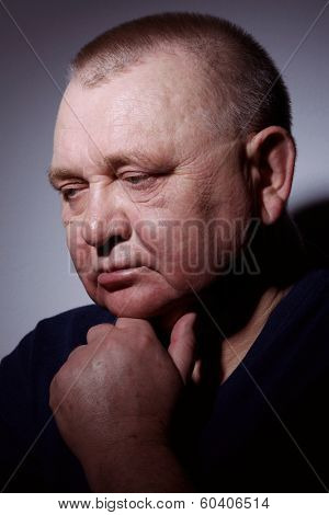 Contrast dramatic close up portrait of thoughtful middle aged man with hand on chin