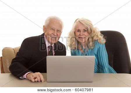 Elderly Couple Laptop Both Looking Smiling