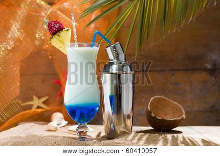 Blue Curacao cocktail with slice of ananas on the beach