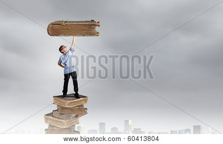 Boy of school age in glasses standing on pile of books