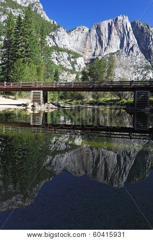 Wooden footbridge over the Merced River in Yosemite Park. In the still water reflected the famous rock monolith, Al Captain
