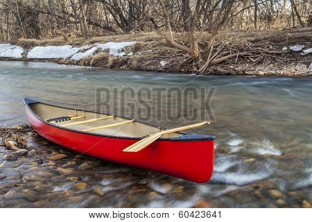 red canoe with a wooden paddle on river shore in winter or early spring - Cache la Poudre River, Fort Collins, Colorado