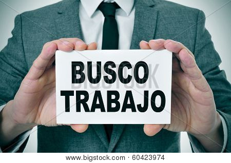 a man wearing a suit holding a signboard with the text busco trabajo, looking for a job written in spanish
