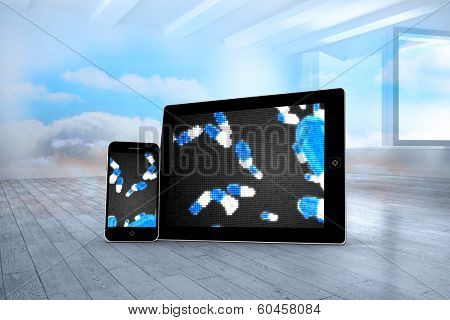Falling pills on tablet and smartphone screens against room with holographic cloud