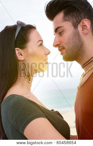 Young loving couple kissing on the beach, side view.