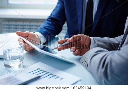 Image of businessmen discussing data in touchpad at meeting