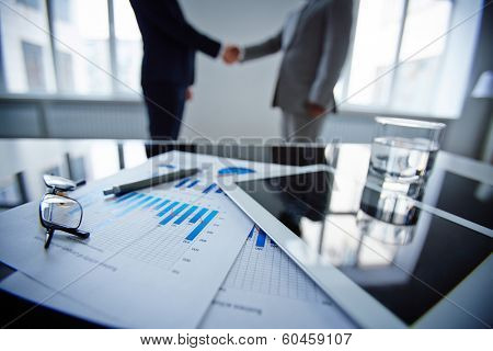 Image of eyeglasses, glass of water, touchpad and financial documents at workplace with businessmen handshaking on background