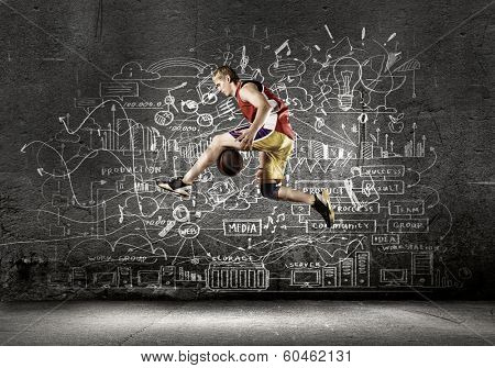 Young man basketball player dribbling ball against black background