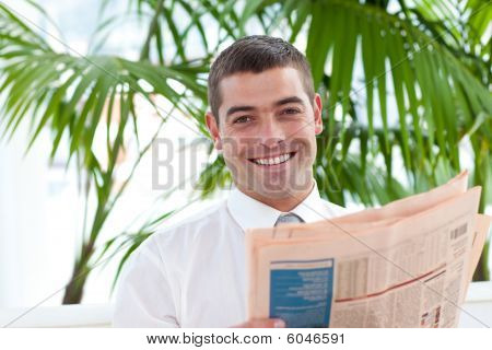 Attractive Businessman Reading A Newspaper In Workplace