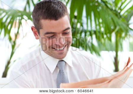 Businessman Reading A Newspaper In Workplace