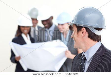 Engenheiro olhando para sua equipe em segundo plano