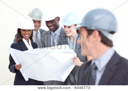 Engineer Looking At His Team Studying A Plan