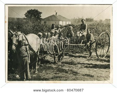 MOSCOW, USSR - CIRCA 1940s : An antique photo shows peasant children, their mother and grandmother. traveling by horse-drawn carriage