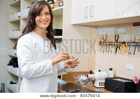 Portrait of happy female optician repairing glasses with screwdriver in workshop