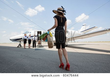 Full length rear view of woman carrying shopping bags while walking towards private jet at airport terminal