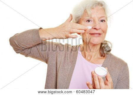 Attractive elderly woman applying lotion to her face