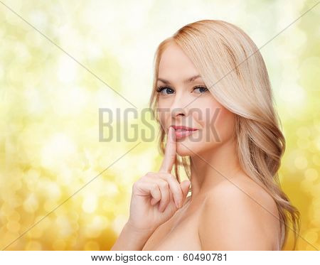 health and beauty concept - clean face of beautiful young woman pointing finger to her lips