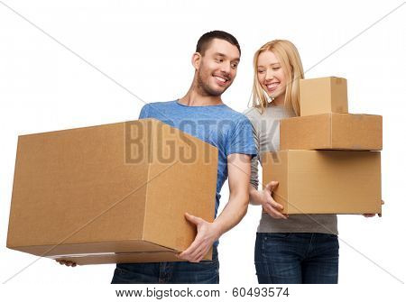 moving, home and family concept - smiling couple holding cardboard boxes