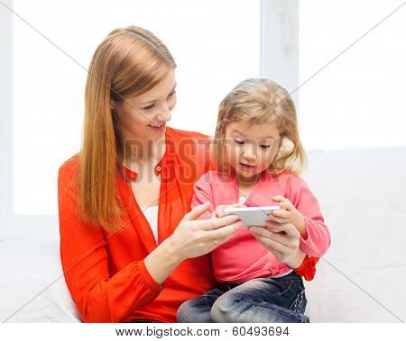 family, children, parenthood, technology and internet concept - happy mother and daughter with smartphone at home