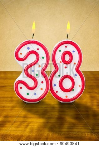 Burning birthday candles number 38 on a wooden background