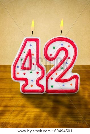 Burning birthday candles number 42 on a wooden background