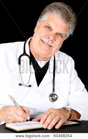 Handsome Mature Blue Eyed Medical Doctor Smiling Writing Prescription