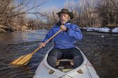foto of collins  - senior canoe paddler in a decked expedition canoe on the Cache la Poudre River - JPG
