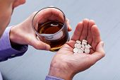 stock photo of suicide  - Man wanting to commit suicide by taking pills with brandy - JPG