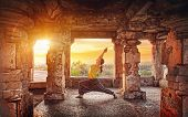 image of stone sculpture  - Woman doing yoga in ruined ancient temple with columns at sunset in Hampi Karnataka India - JPG