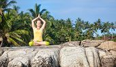 stock photo of mudra  - Woman doing yoga lotus pose on the stone at blue sky and tropical background in Kovalam Kerala India - JPG