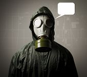 image of rubber mask  - Man wearing a gas mask on his face and a city map behind his back - JPG