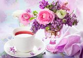 stock photo of vase flowers  - Beautiful spring flowers in vase and cup of tea - JPG