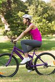 Side view of a fit young woman with helmet riding bicycle at the park